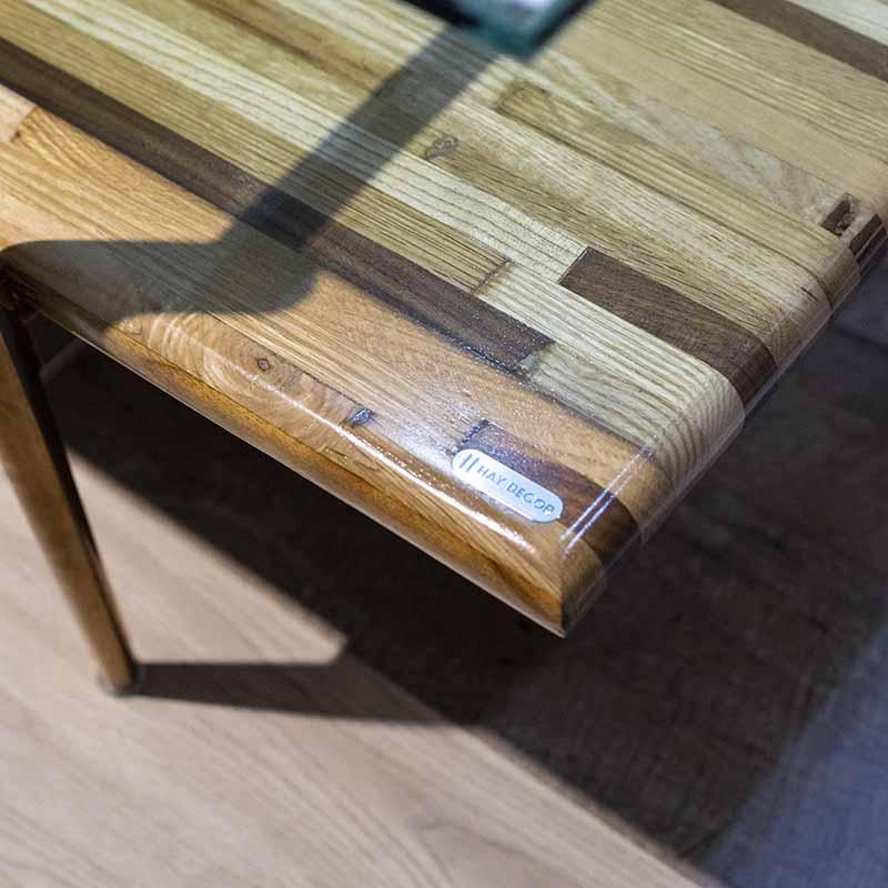Mặt bàn từ nhiều loại gỗ tự nhiên kết hợp (tần bì, sồi, óc chó, beech) và được vát cạnh, sơn phủ bóng loáng, tăng tính thẩm mỹ.