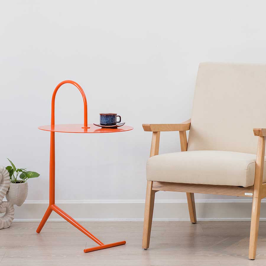 Bàn góc DROOPY orange đặt cạnh ghế bành làm bàn trà xinh xắn.